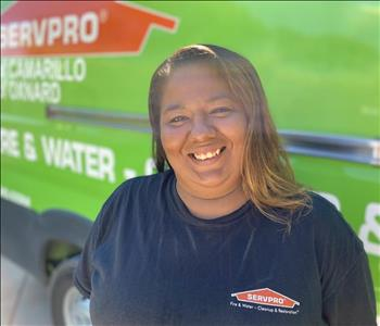 Portrait of Amanda, female employee in front of green truck