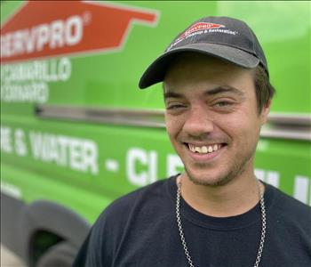 Portrait of Anthony, male employee in front of green truck