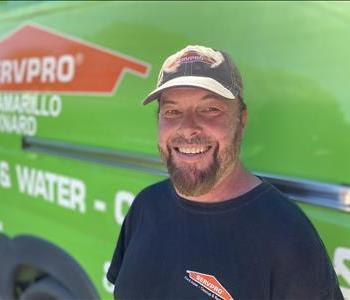 Portrait of male employee Jaison, in front of green truck