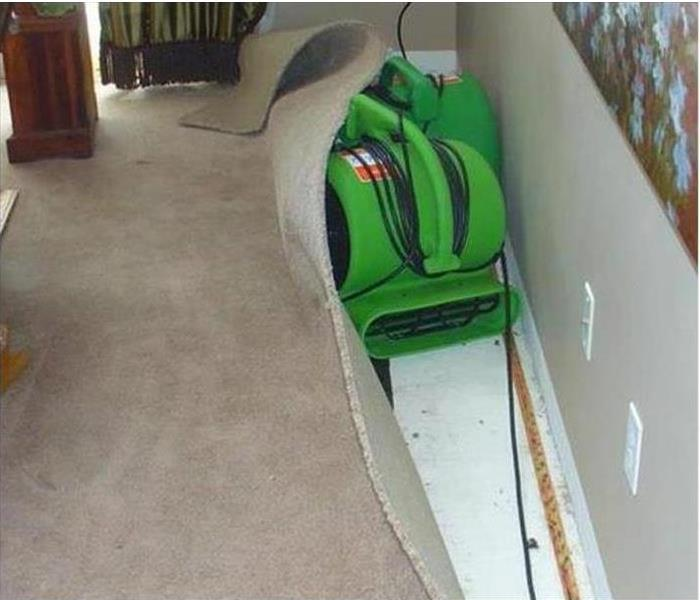 A drying machine being used to fix carpet after water damage